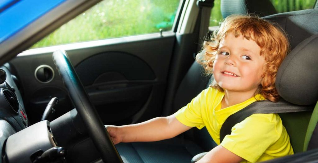 Child sitting in the driver seat of a car