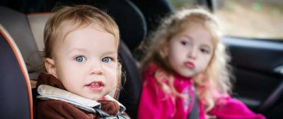 Two kids sitting in the backseat of a car in their car seats.