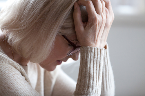 Sad tired senior woman holding head in hands feeling headache